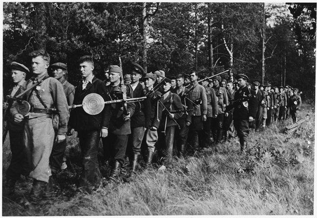 Партизанский отряд в различных мундирах следует за своим командиром в Белоруссии, 1942 год