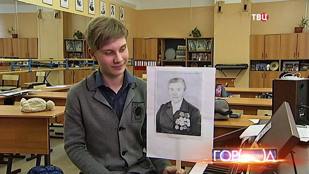 """Участник акции """"Бессмертный полк"""" держит вотографию ветерана"""