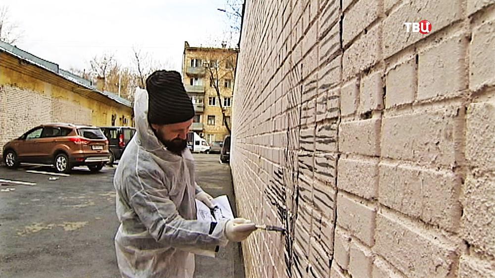 Уличный художник рисует граффити