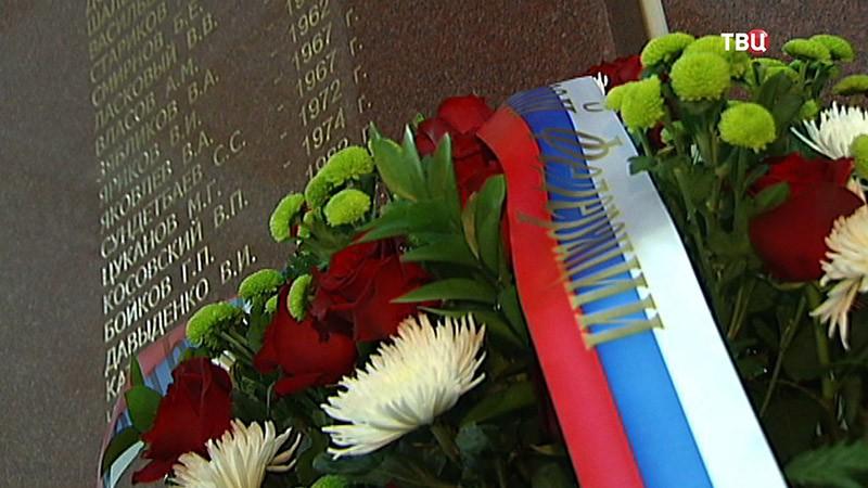 Цветы у мемориальной доски с именами сотрудников ведомств