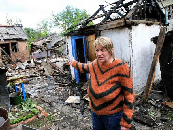 Жительница пригорода Донецка во дворе жилого дома, разрушенного в результате обстрелов украинскими силовиками