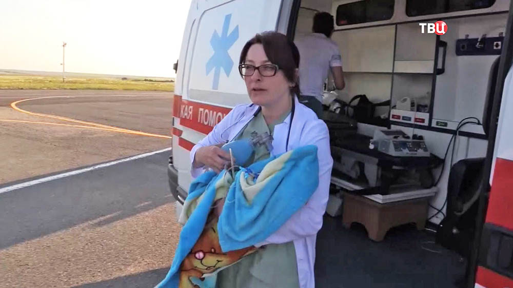 Врач скорой помощи с ребенком на руках