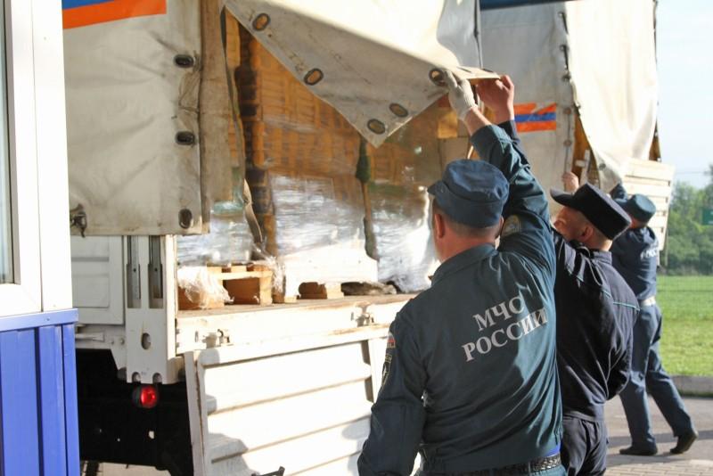 Сотрудники МЧС России во время погрузки гуманитарной помощи на грузовики