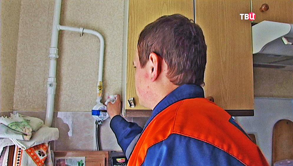 Работник МОСГАЗа проверяет трубы на наличие утечки
