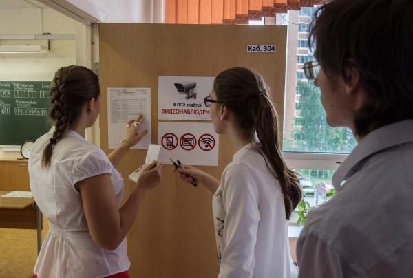 Ученицы смотрят список участников единого государственного экзамена