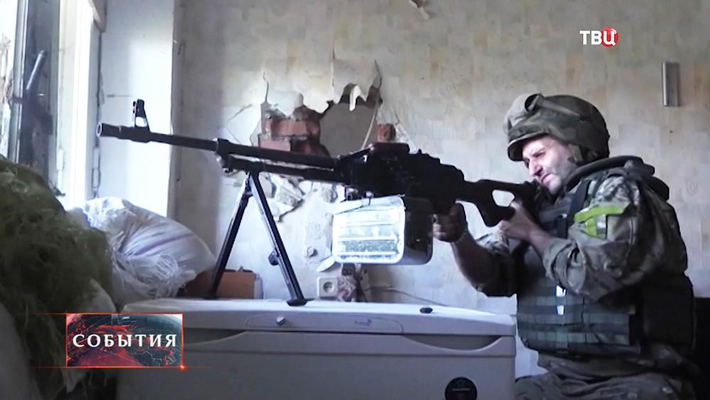 Солдат украинской армии ведет стрельбу из пулемета