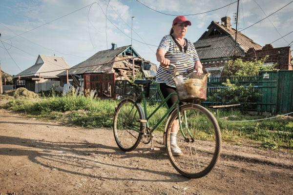 Жительница Донбасса у разрушенных в результате обстрелов домов