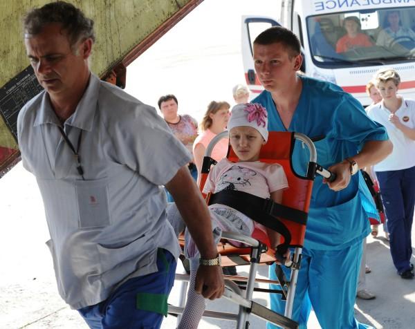 Сотрудники МЧС с ребёнком во время посадки на спецборт