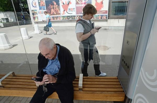 Пассажиры со смартфонами на остановке общественного транспорта