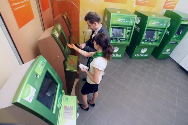 Сотрудница банка консультирует клиента в зоне банкоматного обслуживания