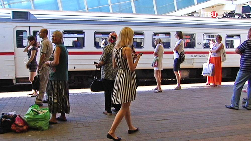 Пассажиры стоят на перроне