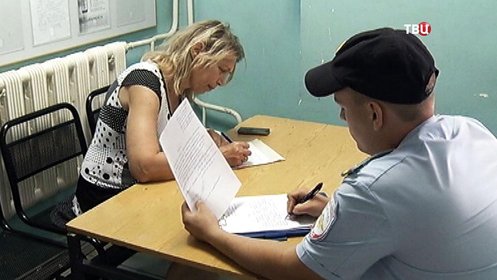 Лариса Кусакина пишет заявление в отделении полиции