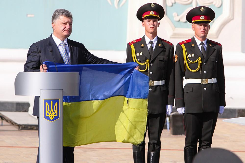 Президент Украины Петр Порошенко держит флаг