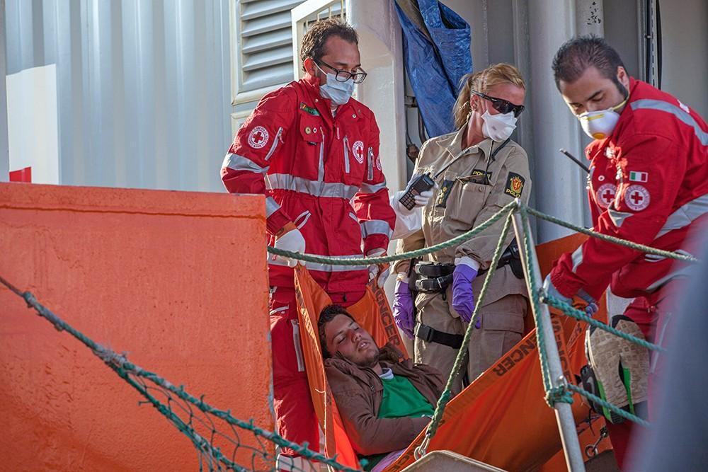 Итальянские спасатели выносят с корабля пострадавшего мигранта