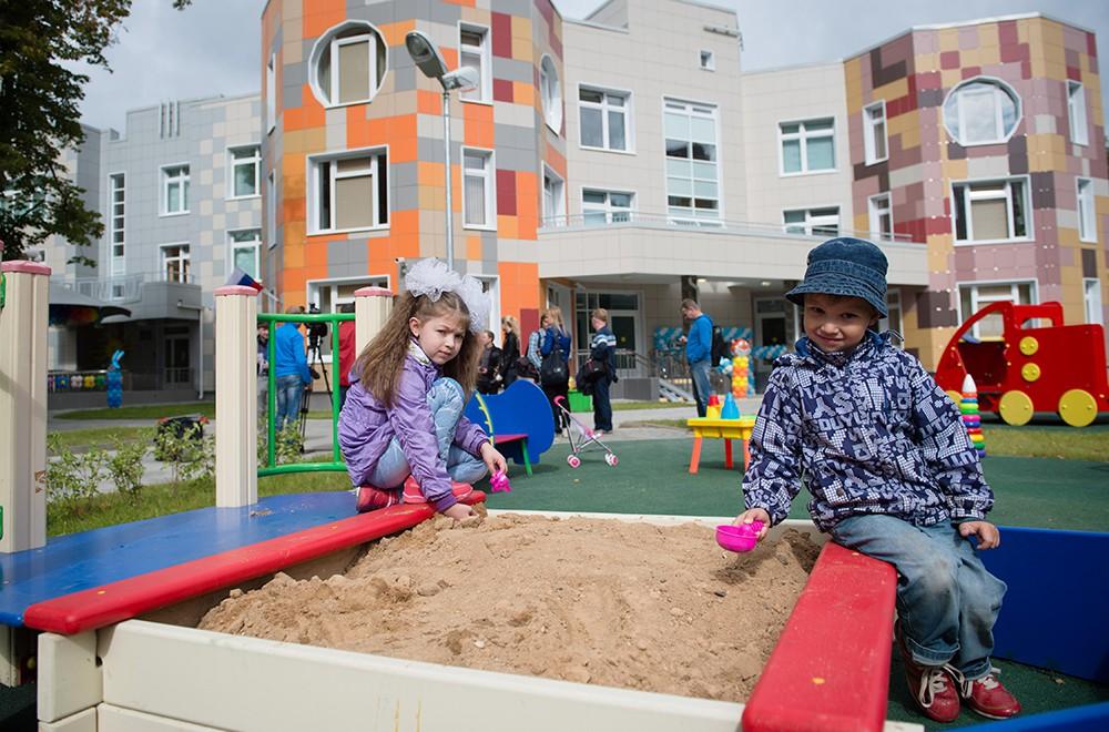 Дети играют на детской площадке возле сада