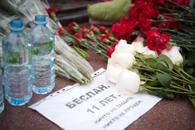 Люди возлагают цветы к памятнику жертвам трагедии в Беслане