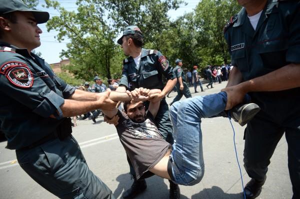 Сотрудники полиции задерживают участника акции протеста в Ереване