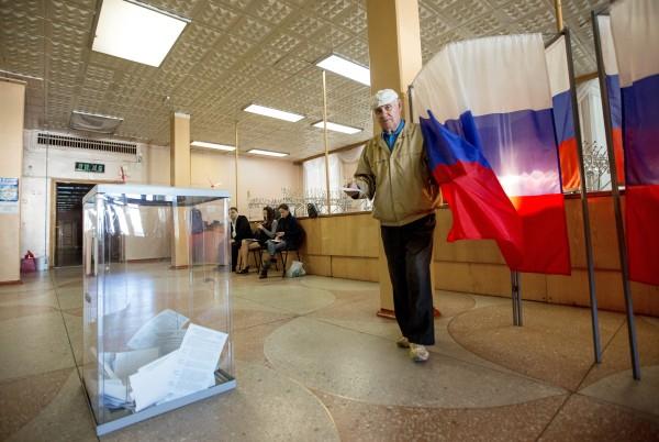 Избиратель голосует на избирательном участке