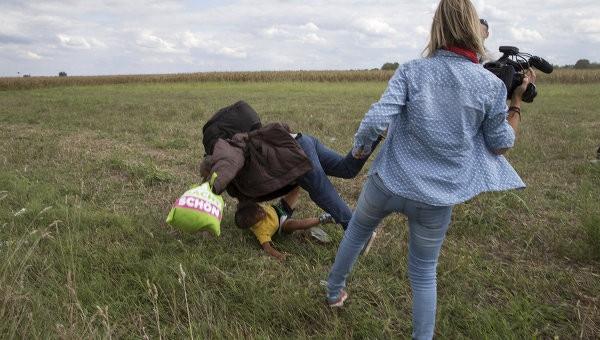 Венгерская журналистка ставит подножку сирийскому беженцу с ребёнком на руках