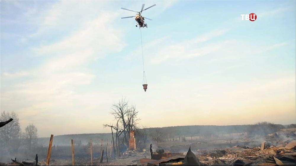 Пожарный вертолёт на месте возгорания в посёлке