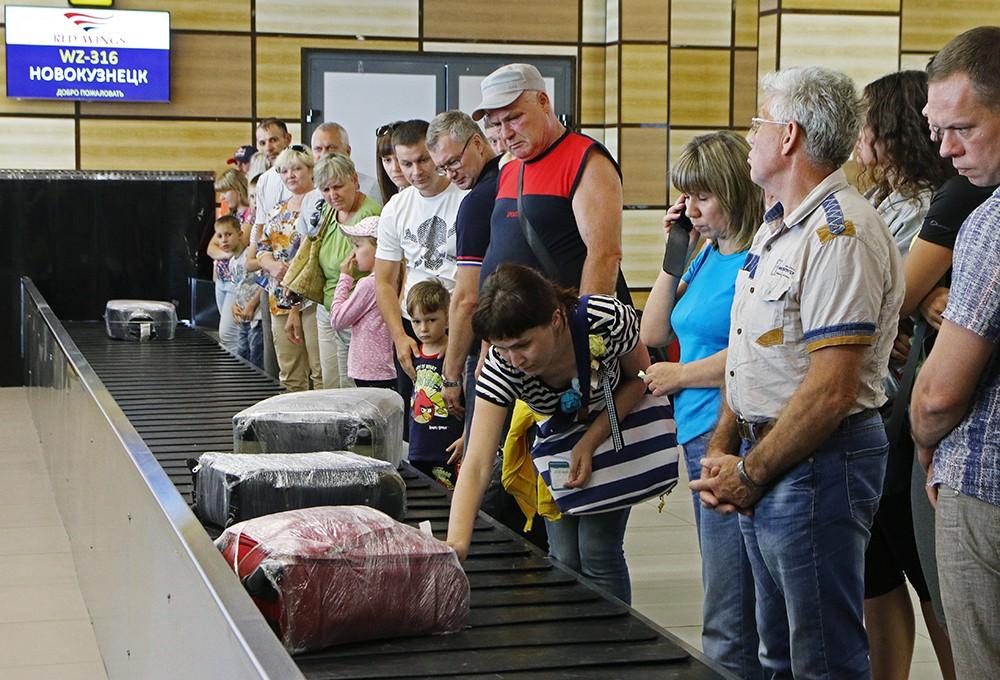 Пассажиры в аэропорту получают багаж