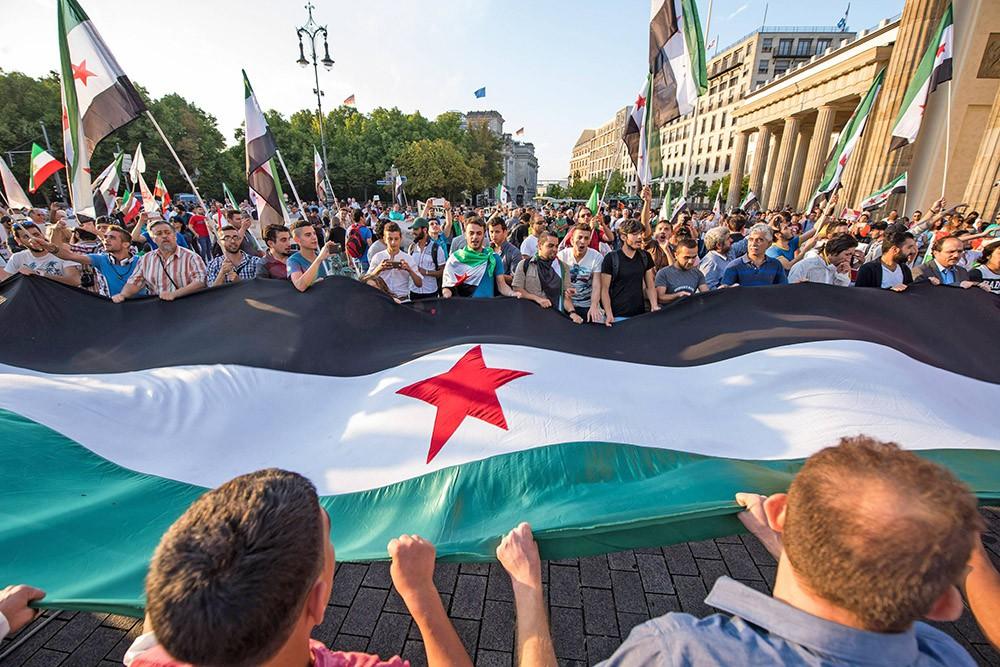 Люди растянули флаг Сирии