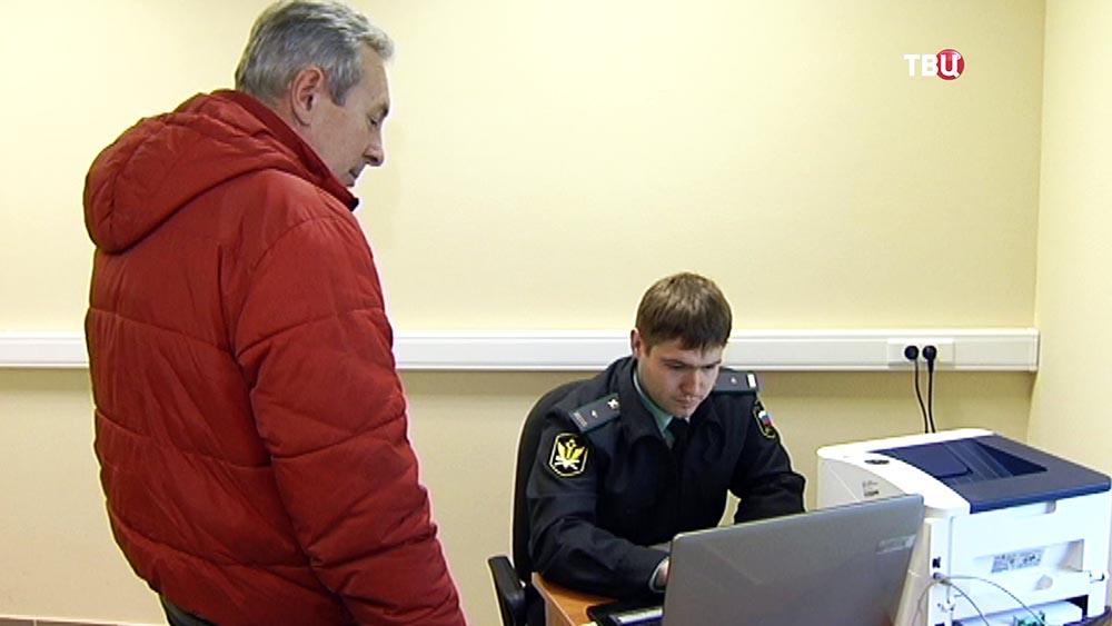 Судебный пристав проверяет мужчину по базе должников