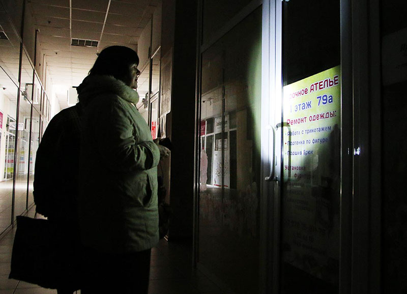 Женщина у закрытого, из-за отсутствия электричества, ателье по ремонту одежды в Симферополе