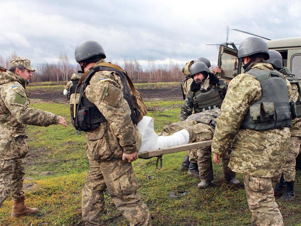Украинские военные несут раненного на носилках
