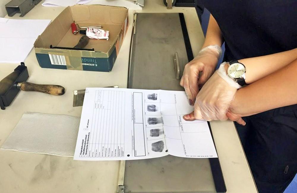 Полиция Германии снимает отпечатки пальцев с задержанных
