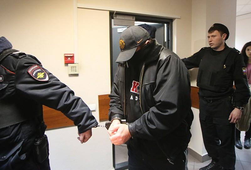 Сотрудники полиции ведут Александра Величко, подозреваемого в убийстве