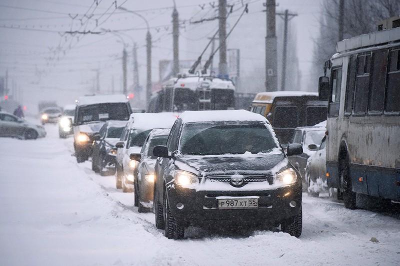 Автомобили во время сильного снегопада на одной из улиц города Омска