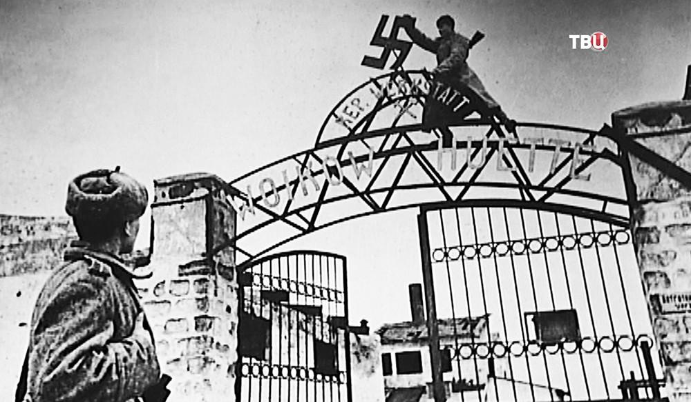 Советские солдаты снимают фашистский крест с ворот концлагеря