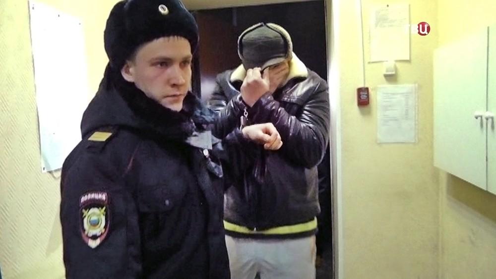 Полицейский ведет задержанного ульяновского коллектора-поджигателя Дмитрия Ермилова