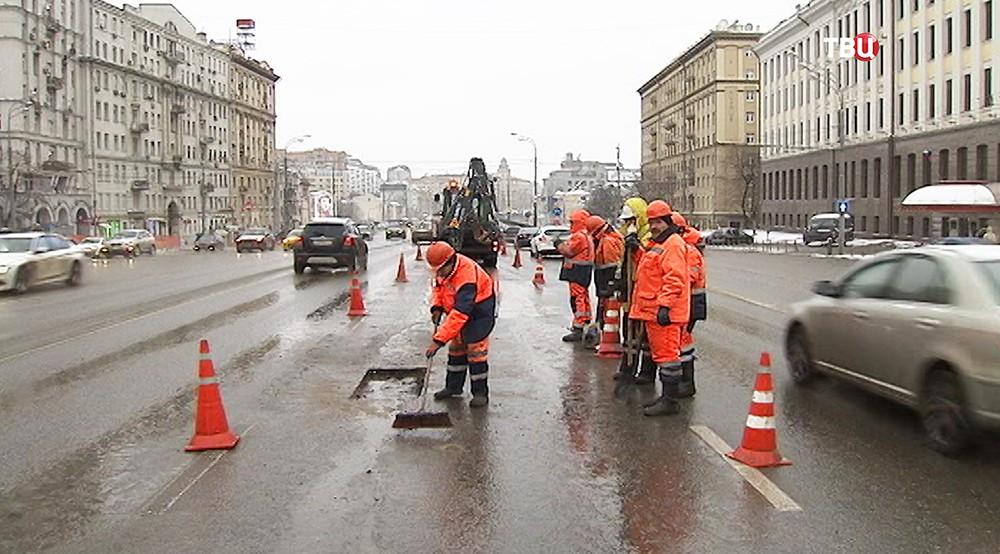 Сотрудники коммунальной службы во время ремонта дороги