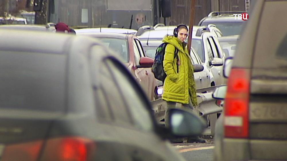 Человек на пешеходном переходе в потоке машин