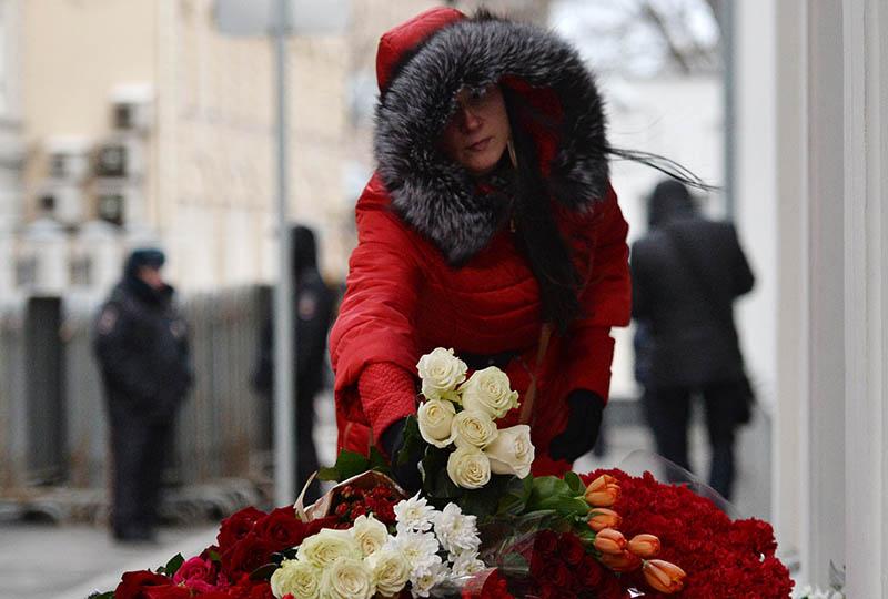 Женщина возлагает цветы у посольства Бельгии в Москве