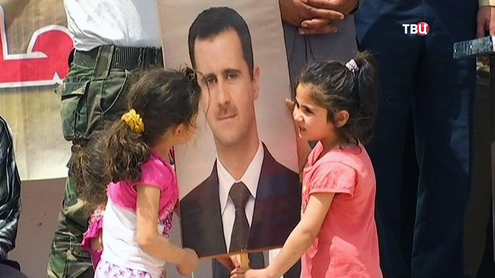 Сирийские дети держат портрет Башара Асада