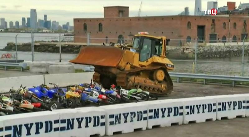 Бульдозер уничтожает десятки конфискованных мотоциклов