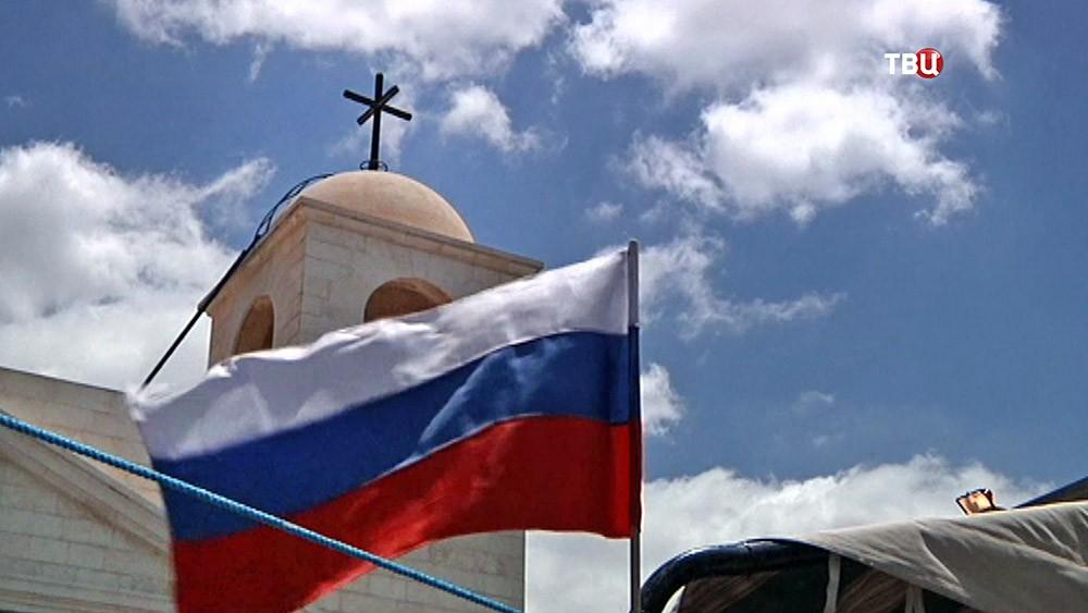 Российский флаг на фоне православного храма в Сирии