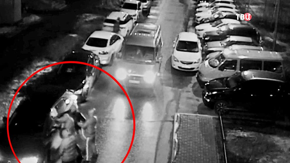 Грабители разбивают окно автомобиля