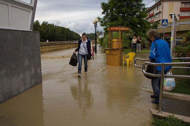 Жители идут по улице Сочи после проливного дождя