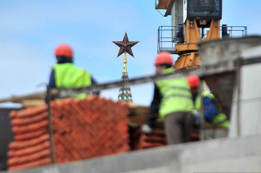 Строители на фоне Кремля