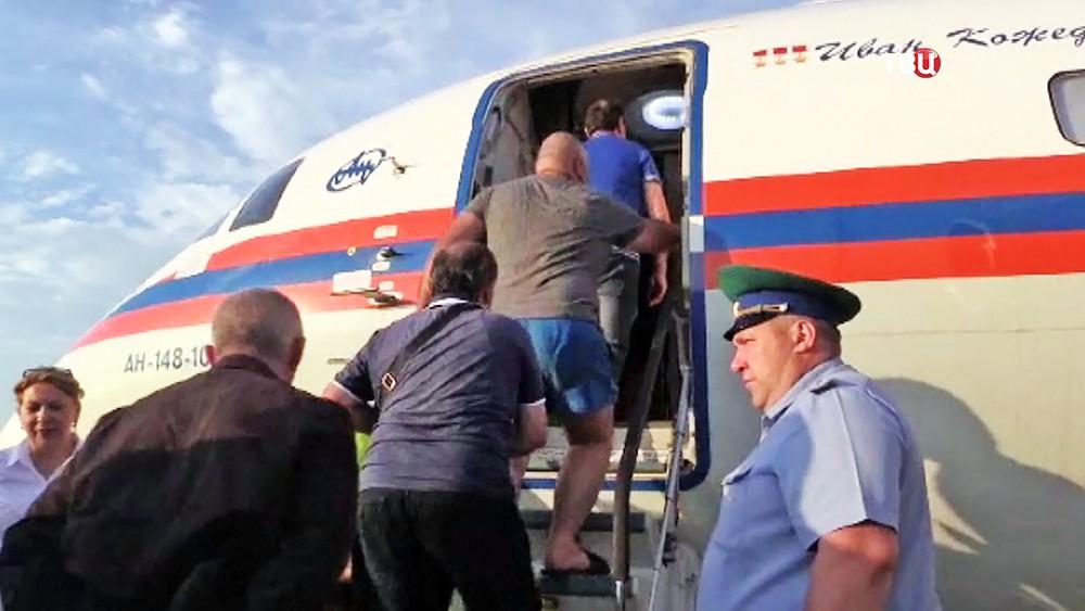 Пассажиры поднимаются на борт самолета МЧС