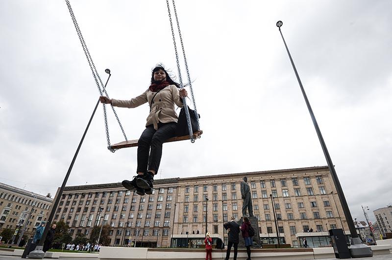 Девушка катается на качелях на Триумфальной площади в Москве