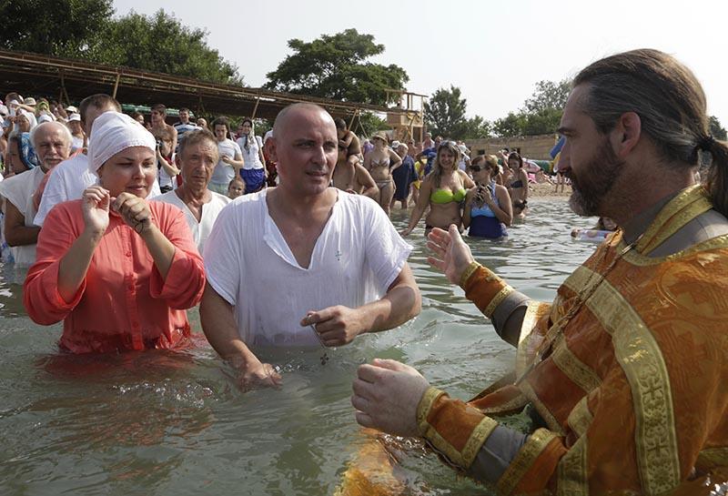 Священнослужители проводят обряд крещения верующих