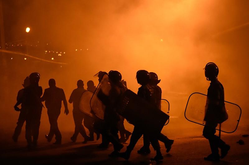 Полицейские во время столкновения с протестующими на улице близ захваченного в Ереване здания полка патрульно-постовой службы