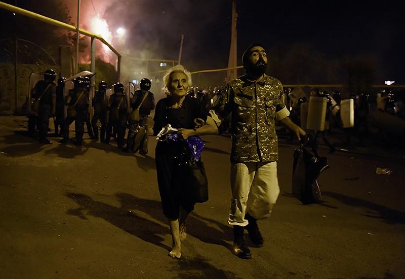 Мужчина уводит пожилую женщину с места столкновения протестующих с полицейскими на улице близ захваченного в Ереване здания полка патрульно-постовой службы