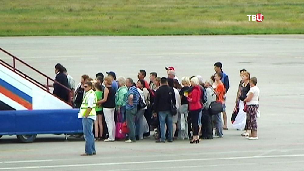 Пассажиры возле трапа самолета