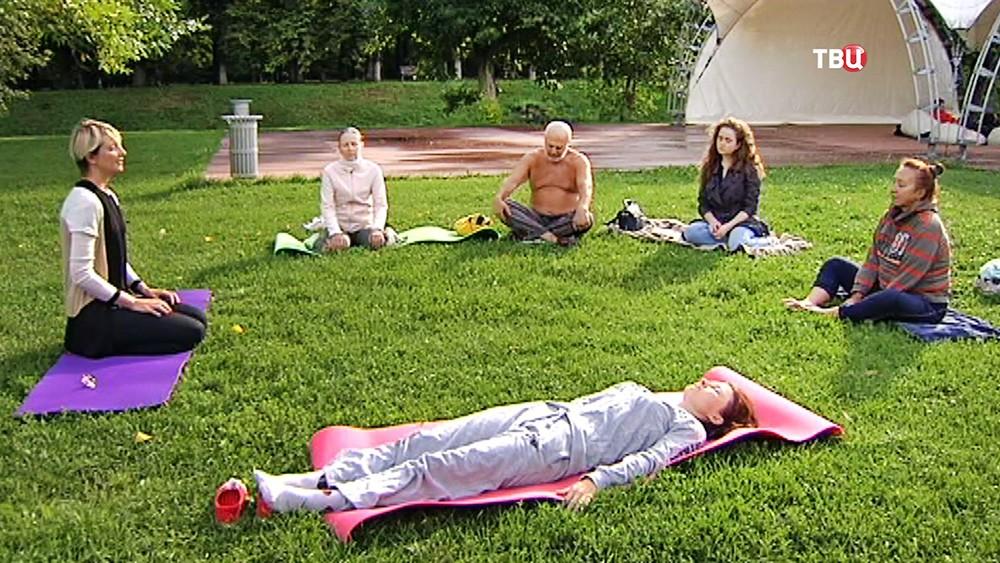 Люди медитируют в парке